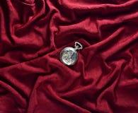 在红色丝绸背景的古色古香的闭合的金黄怀表 库存图片