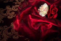 在红色丝绸物质背景的两朵丝绸花 库存图片