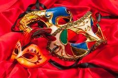 在红色丝绸的三个狂欢节面具 免版税库存图片