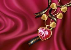 在红色丝绸的项链心脏。 免版税图库摄影