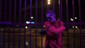 在红色体育成套装备和太阳镜穿戴的滑稽的男性在晚上有效地唱歌 股票视频