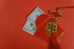 在红色信封春节问候礼物的金钱,关闭了在红色传统信封的美元钞票 库存照片