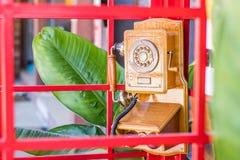 在红色内阁的老电话 库存照片