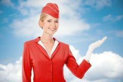 在红色制服打扮的迷人的空中小姐在手中举行 库存图片