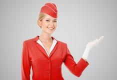 在红色制服打扮的迷人的空中小姐在手中举行 免版税库存图片