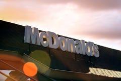 在红色剧烈的日落天空背景的McDonalds商标 它是世界` s最大的快餐ch 免版税库存图片