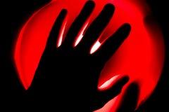 在红色发光的背景的手 库存图片