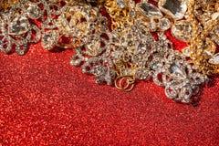 在红色发光的闪烁背景的金黄和银色首饰 免版税库存图片