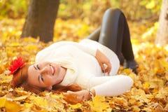 在红色叶子中的妇女在秋天森林里 库存图片