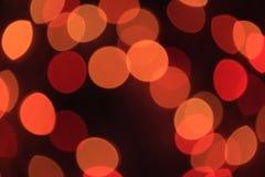 在红色和橙色颜色光外面焦点,被弄脏, Bokeh在黑暗的抽象背景的 免版税图库摄影