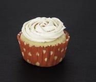 在红色和白色划线员的香草杯形蛋糕 免版税库存图片