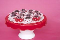 在红色和白色小点划线员的巧克力蛋糕球在红色板材pi 图库摄影