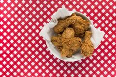 在红色和白色方格的桌上的炸鸡篮子 图库摄影