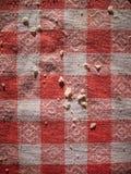 在红色和白色方格的桌布的面包屑 库存图片