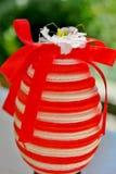 在红色和白色条纹的鸡蛋与一条红色丝带和一朵小花 免版税库存图片
