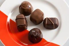 在红色和白色板材的巧克力糖 库存图片