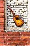 在红色和白色砖背景的声学吉他 图库摄影