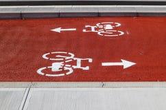 在红色和白色绘的双向周期车道 定向箭头,在自行车标志以后,表明相反方向 免版税库存图片