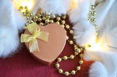 在红色和白色背景的金黄心脏形状礼物箱子 库存图片