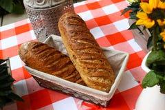 在红色和白色表早餐的面包与花 免版税图库摄影