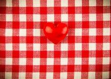 在红色和白细胞的纺织品纹理与一红色心脏 免版税库存照片