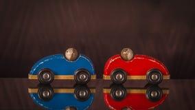 在红色和蓝色的两辆木玩具汽车与人 库存照片