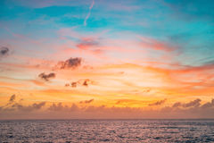 在红色和蓝色颜色的日落天空与在海天线的微妙的云彩 免版税库存图片