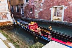 在红色和金黄装饰的传统长平底船在威尼斯绿色运河,意大利 免版税库存照片