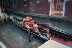 在红色和金黄装饰的传统长平底船在威尼斯绿色运河,意大利 免版税库存图片