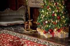 在红色和金黄颜色装饰的时髦的圣诞节内部 库存照片