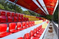 在红色和黄色的空的街道位子在指挥台在观看体育比赛的机盖下 库存照片