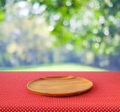 在红色圆点桌布的空的圆的木盘子在迷离tr 免版税库存照片