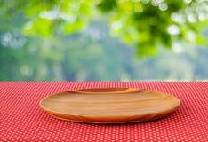 在红色圆点桌布的空的圆的木盘子在迷离tr 图库摄影