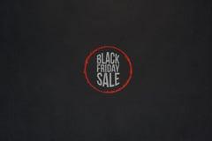 在红色圈子的黑星期五销售文本在黑暗的纸 免版税库存图片