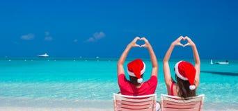 在红色圣诞老人帽子的愉快的浪漫夫妇在海滩 库存照片