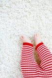 在红色圣诞老人长裤的婴孩身体特写镜头和腿在圣诞节 免版税库存照片