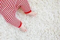 在红色圣诞老人长裤的婴孩身体特写镜头和腿在圣诞节 免版税库存图片