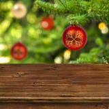 在红色圣诞节球背景的木桌 免版税库存图片