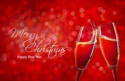 在红色圣诞节背景的两块香槟玻璃 免版税库存图片