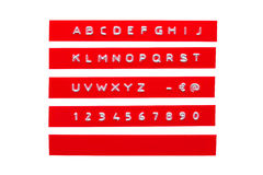 在红色塑料磁带上的压印的字母表 库存照片