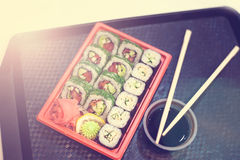 在红色塑胶容器的日本寿司在黑色的运载的食物的 卷由蟹肉,鲕梨,里面的黄瓜制成和 库存图片