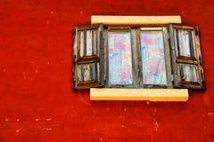 在红色墙壁上的木窗口 库存图片