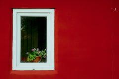 在红色墙壁上的白色窗口在街道上 图库摄影