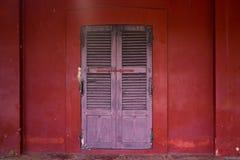 在红色墙壁上的老木门 免版税库存图片