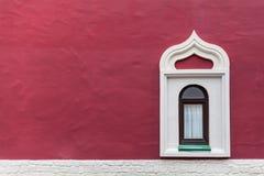 在红色墙壁上的背景窗口 免版税库存照片