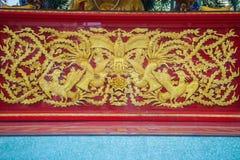 在红色墙壁上刻记的美丽的金黄中国人菲尼斯鸟 免版税库存照片