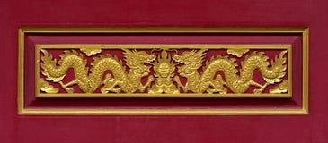 在红色墙壁中国式雕刻的木头 免版税库存照片