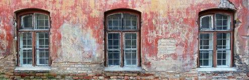 在红色墙壁的三个腐烂的弯曲的窗口一被破坏的老bric 免版税库存图片