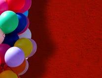 在红色墙壁附近的气球 免版税图库摄影