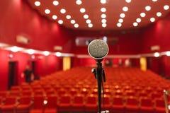 在红色大厅背景的话筒有就座的观众的 库存图片